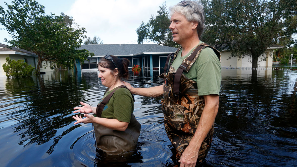 Kelly McClenthen walks through floodwaters with her boyfriend Daniel Harrison, after checking on her flooded home, in the aftermath of Hurricane Irma, which passed through yesterday, in Bonita Springs, Fla., Monday, Sept. 11, 2017.