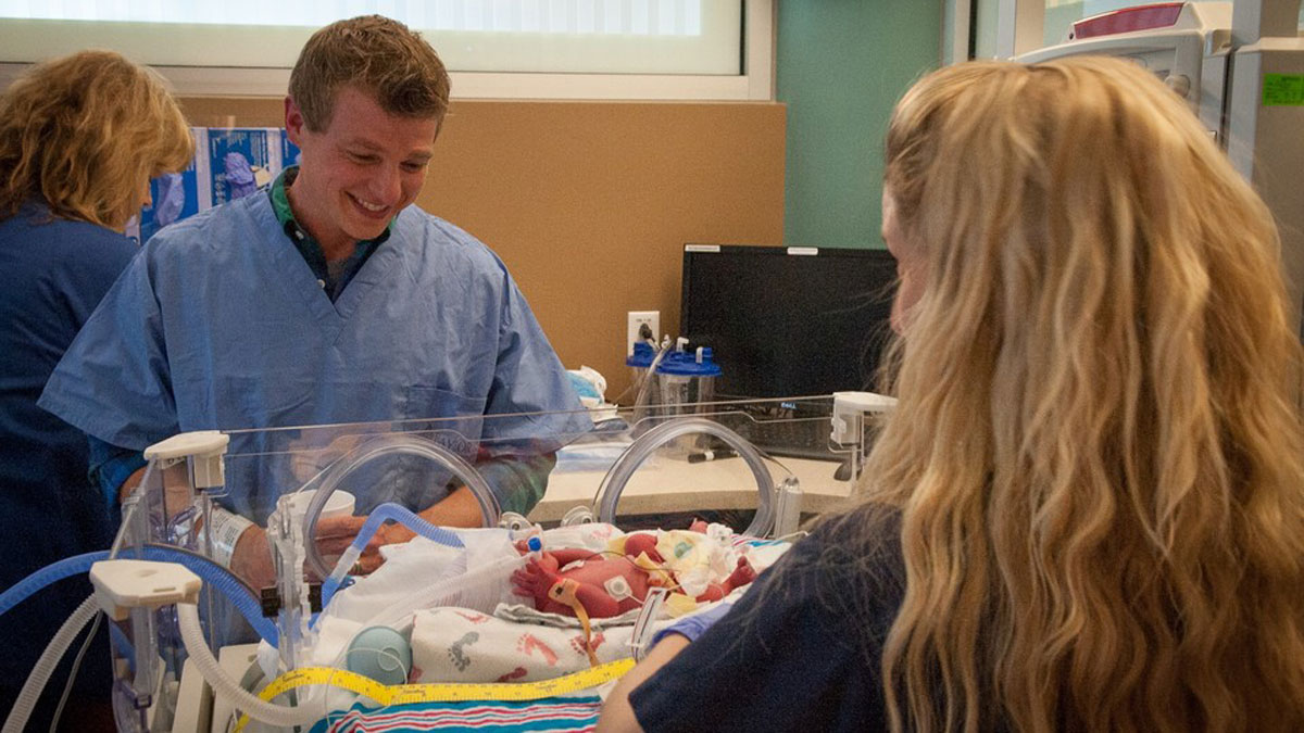 Elizabeth Watkins, RN, settles one of the quads born to Joshua and Anna Hall, of Fort Worth, into the NICU while dad watches. The four babies were delivered at Baylor Regional Medical Center at Grapevine on May 5, 2014.