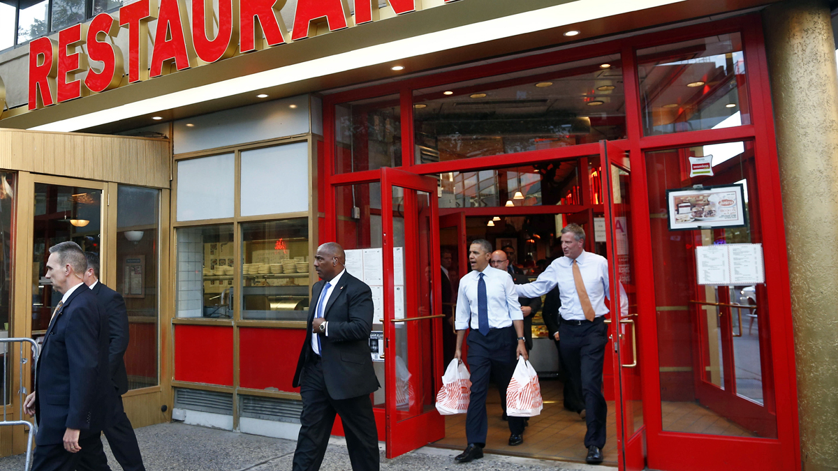 Carrying a takeout order of cheesecake, President Barack Obama and then New York City Democratic Mayoral Candidate Bill de Blasio leave after they visited Junior's Cheesecake restaurant in the borough of Brooklyn, New York, Friday, Oct. 25, 2013. (AP Photo/Charles Dharapak)