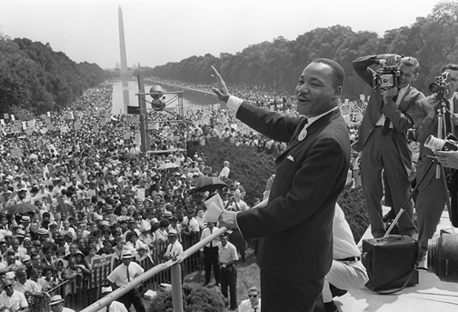Martin Luther King waves to supporters 28 August 1963 on the Mall in Washington DC (Washington Monument in background) during the
