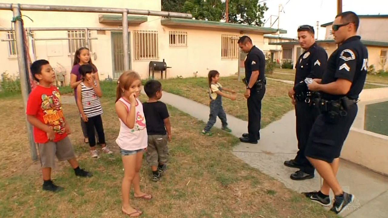 LAPD officers assigned to patrol the Jordan Downs Housing Projects interact with children before the 50th anniversary of the Watts riots.