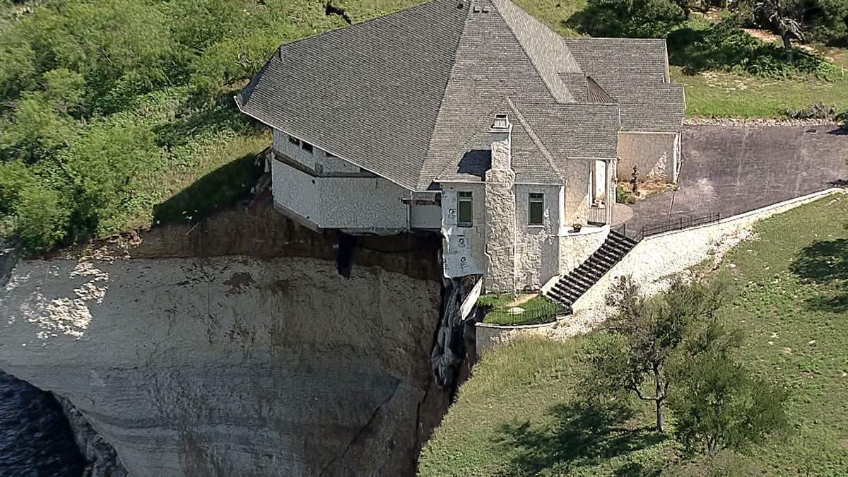 A large home built on a cliff overlooking Lake Whitney is in danger of falling into the lake after a large chunk of the ground underneath the home slid into the lake below.