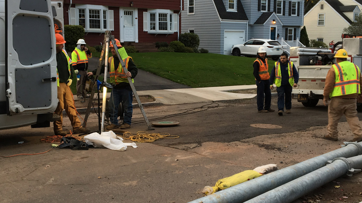 Metropolitan District Commission crews work Thursday morning to install a new sewer pipe liner nearly three weeks after another liner failed, allowing sewage to back up into homes on Linwood Road.