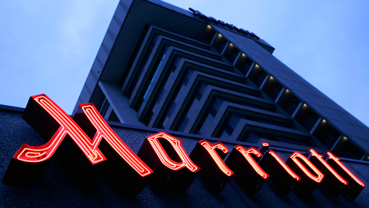 The Marriott sign glows outside the hotel Saturday, Feb. 4, 2006, in Salt Lake City, file photo. The Marriott and Starwood merger closed Friday morning.