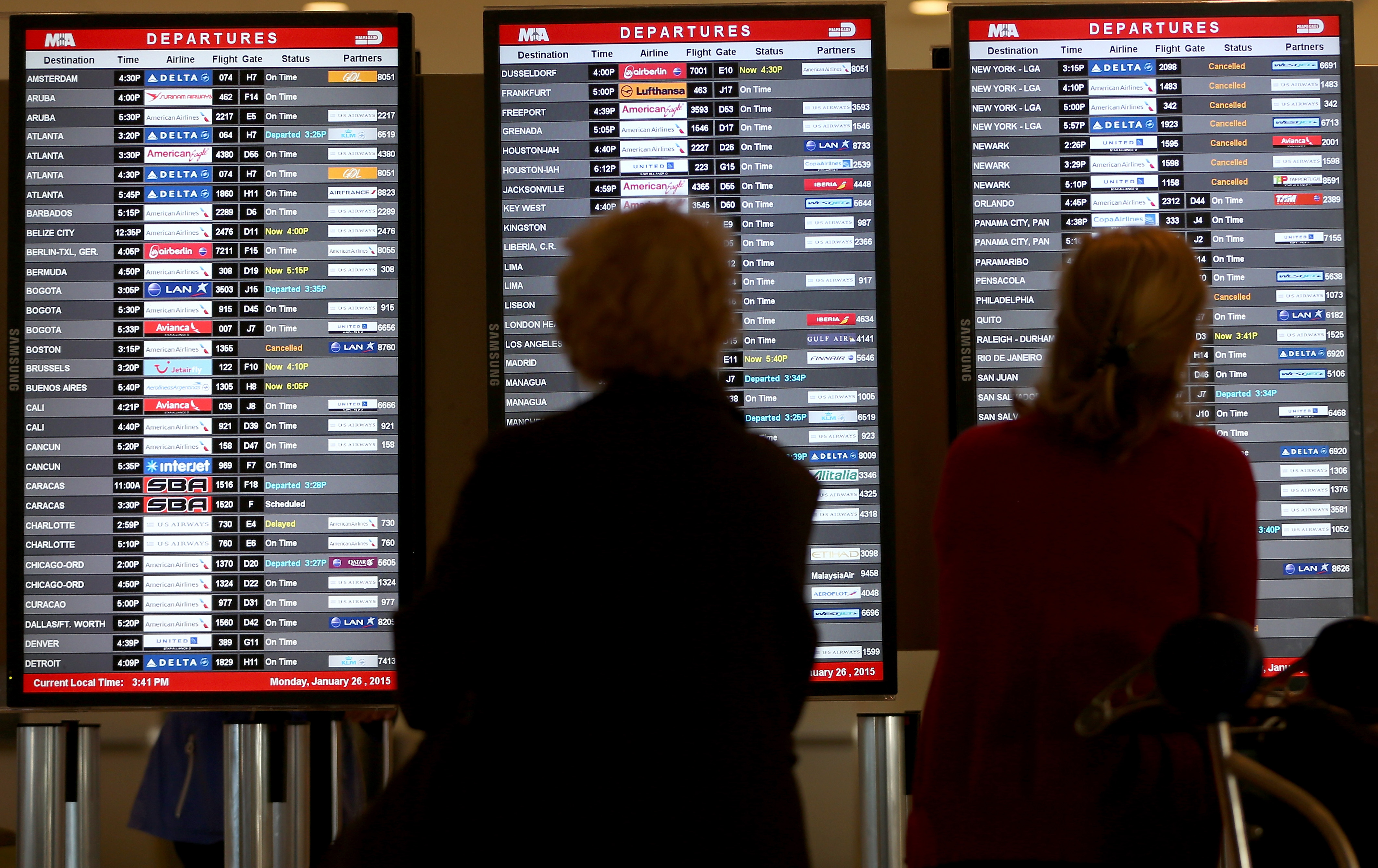 In this file photo, passengers look at a departure board at Miami International Airport. Airlines began expanding their Hurricane Irma change-fee waivers to include Florida airports as the storm appeared increasingly likely to track toward the state.