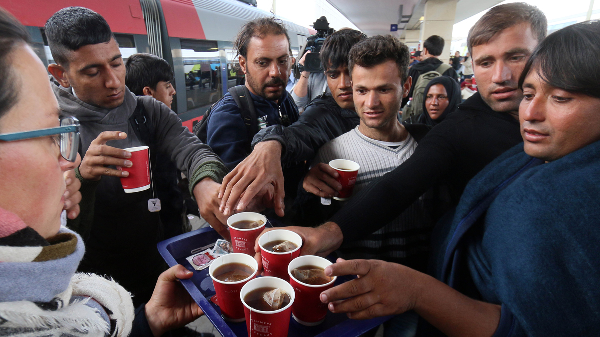Migrants get some tea as they arrive at the Westbahnhof station in Vienna, Austria, Sunday, Sept. 6, 2015. Since Saturday more than 7,000 Arab and Asian asylum seekers surged across Hungary's western border into Austria and Germany.