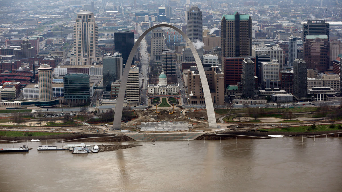 In this aerial photo, the Mississippi River flows past the Gateway Arch Wednesday, Dec. 30, 2015, in St. Louis. A rare winter flood threatened nearly two dozen federal levees in Missouri and Illinois on Wednesday as rivers rose, prompting evacuations in several places.
