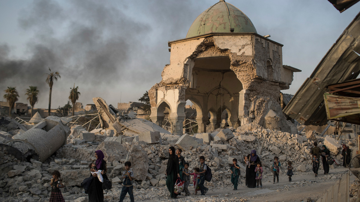 Fleeing Iraqi civilians walk past the heavily damaged al-Nuri mosque as Iraqi forces continue their advance against Islamic State militants in the Old City of Mosul, Iraq, Tuesday, July 4, 2017.