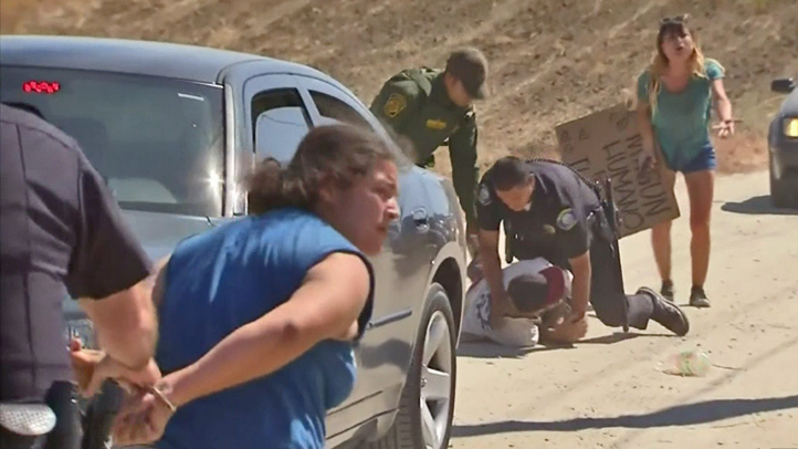 Officers make arrests as a scuffle broke out between demonstrators outside a Murrieta Border Patrol facility where dozens of undocumented immigrants were expected to arrive for processing on Friday, July 4, 2014.