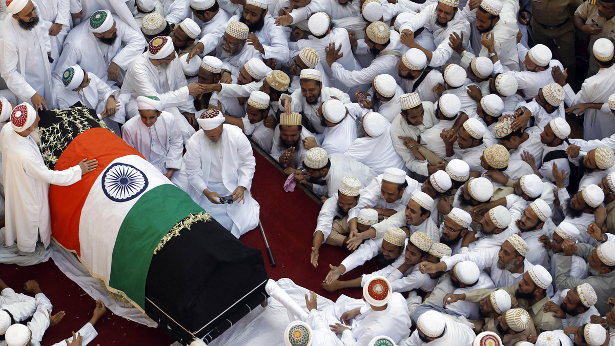 Indian Muslims stretch out their hands towards the body of the head of the Dawoodi Bohra Muslim community Syedna Mohammed Burhanuddin during his funeral procession in Mumbai, India, Saturday, Jan. 18, 2014. A pre-dawn stampede killed more than a dozen people Saturday as tens of thousands of people gathered to mourn the death of Muslim spiritual leader Burhanuddin in the India's financial capital, police said. Burhanuddin died Friday at the age of 102.
