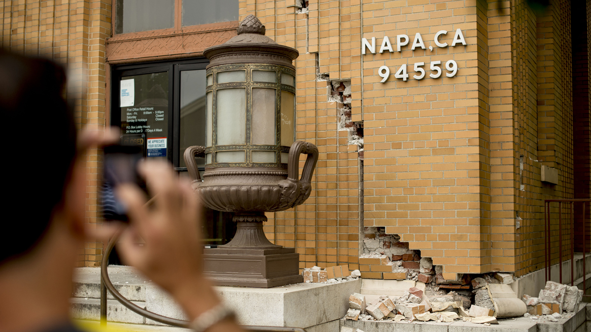 A man photographs damage to a post office in Napa, Calif., following an earthquake Sunday, Aug. 24, 2014.