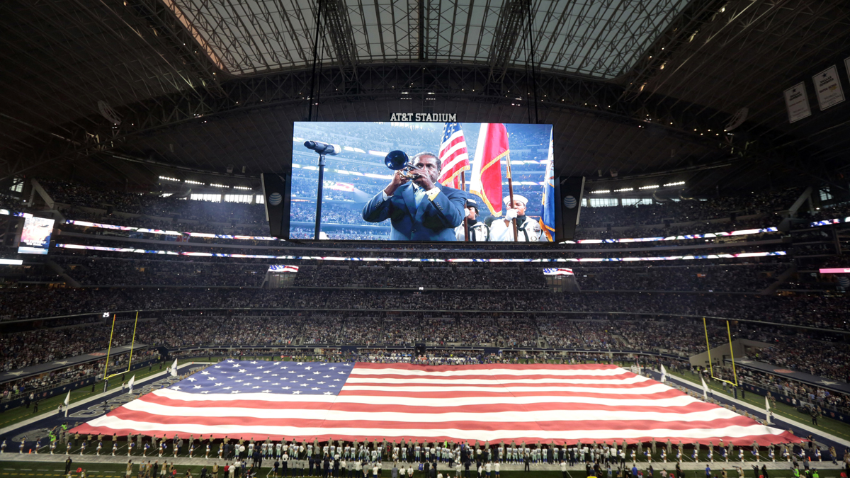 In this Sept. 13, 2015, photo, U.S. service personnel unfurl a field-sized United States flag inside AT&T Stadium as a trumpeter plays the national anthem before an NFL football game between the New York Giants and the Dallas Cowboys in Arlington, Texas.