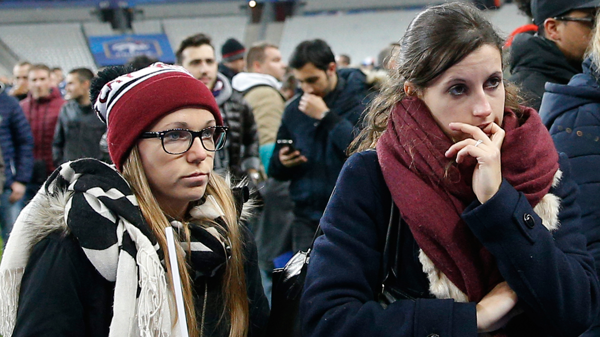 Soccer fans wait on the pitch of the Stade de France stadium on Friday, Nov. 13, 2015, following an explosion that occurred outside the stadium.