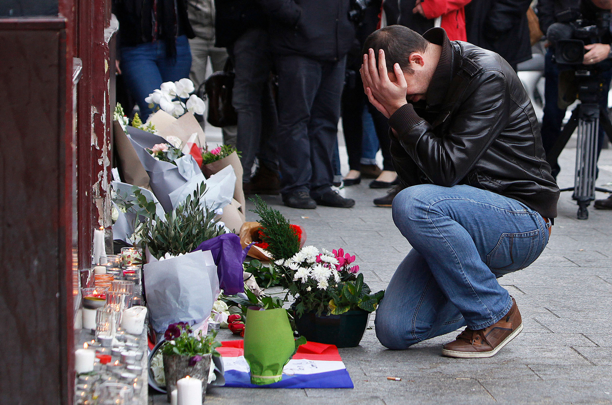 File photo: A man holds his head in his hands as he lays flowers in front of the Carillon cafe, in Paris, Saturday, Nov.14, 2015.