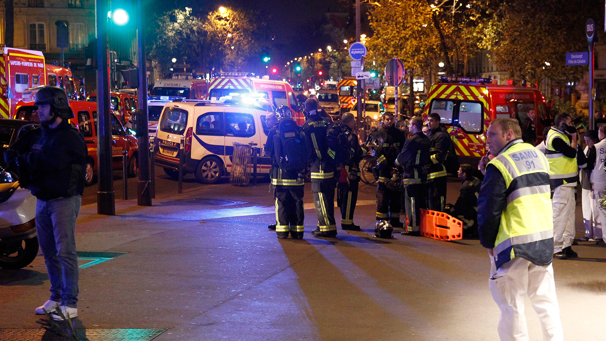 Police and medics gather near the Boulevard des Filles-du-Calvaire after an attack November 13, 2015 in Paris, France. Gunfire and explosions in multiple locations erupted in the French capital, leaving dozens dead.