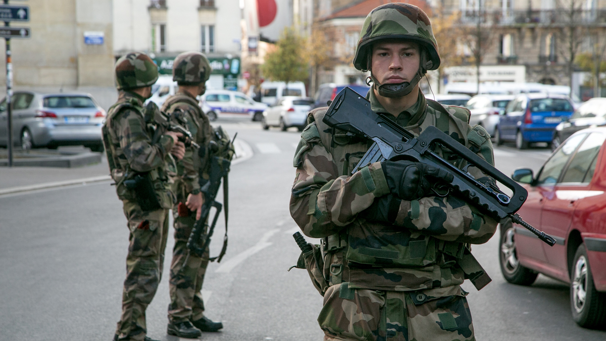 French soldiers stand guard on 'Rue de la Republique' on November 18, 2015 in Saint-Denis, France. French Police special forces raided an apartment, hunting those behind the attacks that claimed 129 lives in the French capital five days ago. At least one person was killed in an apartment targeted during the operation aimed at the suspected mastermind of the attacks, Belgian Abdelhamid Abaaoud. At least five police officers were been wounded in the shootout.