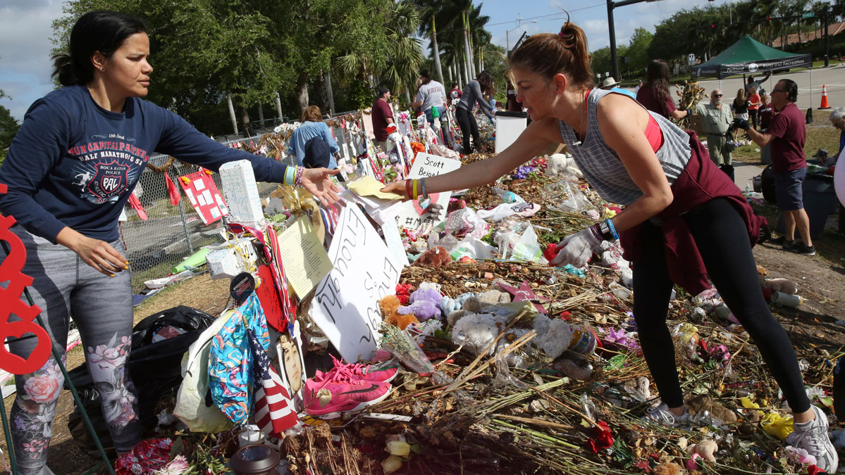 Patricia Padauy, right, passes a handwritten note to her friend Sharamy Angarita, as they clean and sort out items at the memorial site of Padauy's son Joaquin Oliver in Parkland, Fla., Wednesday, March 28, 2018.