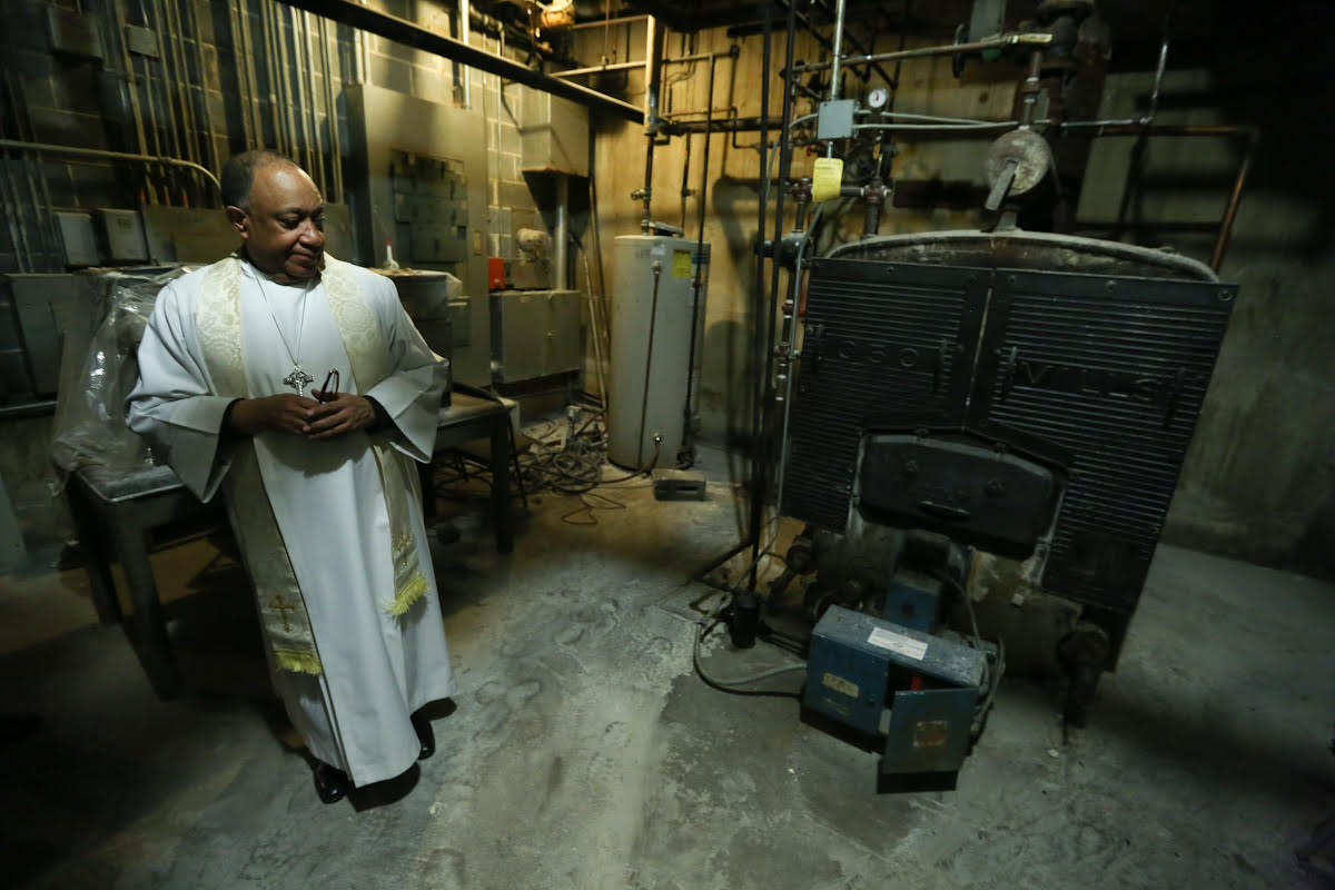 In this photo provided by BlocPower, Reverend Leo W. Curry stands in the basement of the Fordham United Methodist Church in the Bronx, New York, with a boiler that will be replaced with an energy-efficient boiler as part of a BlocPower project.