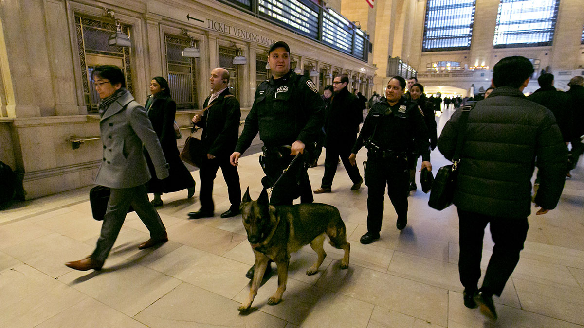 Metro-North Railroad police officers patrol Grand Central Terminal in New York Tuesday. Authorities are increasing security throughout New York City following explosions at the airport and subway system in the Belgian capital of Brussels.