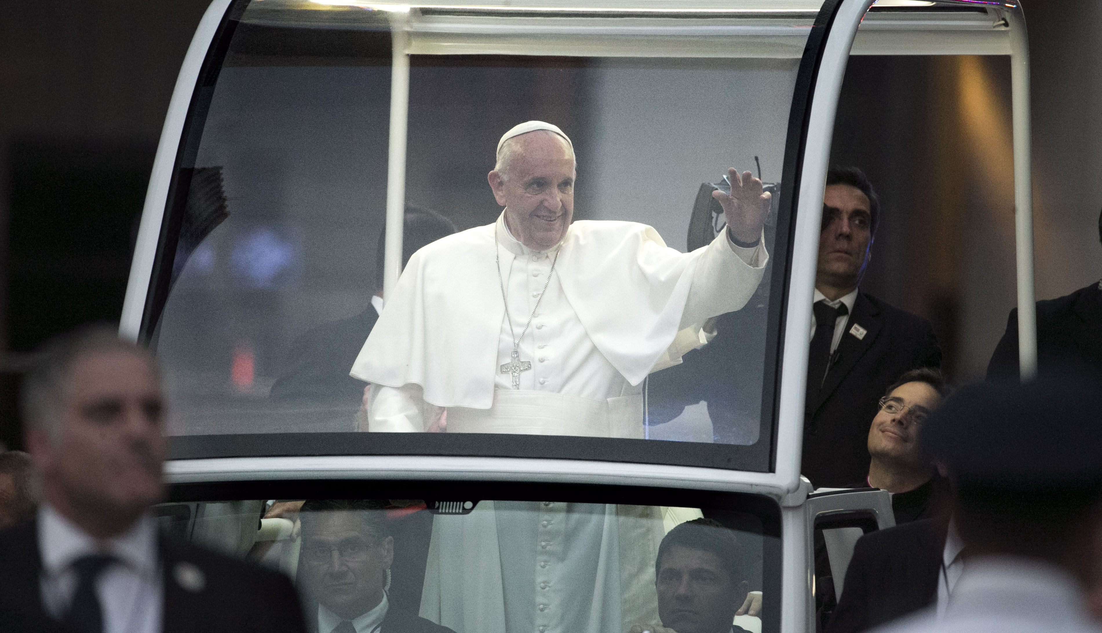 Pope Francis waves to people gathered on the street as he is driven through New York City to St. Patrick's Cathedral to conduct an evening prayer service, Thursday, Sept. 14, 2015. (Aristide Economopoulos/The Star Ledger via AP, Pool)