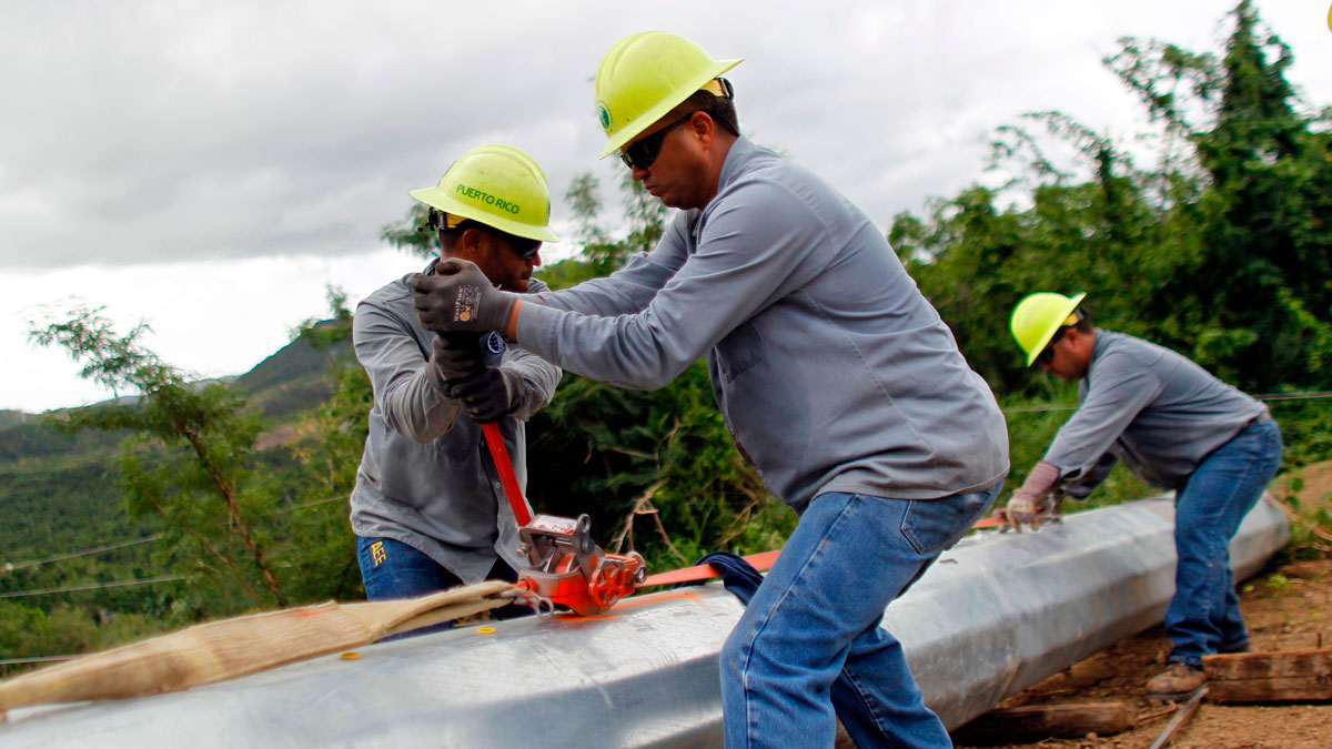 A Puerto Rico Electric and Power Authority brigade work in a remote off-road location to repair a downed power transmission line in Ponce, Puerto Rico on November 29, 2017