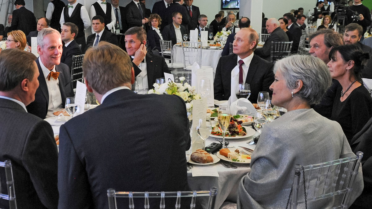 File Photo—In this file photo taken on Thursday, Dec. 10, 2015, Russian President Vladimir Putin, center right, with retired U.S. Lt. Gen. Michael T. Flynn, center left, and Serbian filmmaker Emir Kusturica, obscured second right, attend an exhibition marking the 10th anniversary of RT (Russia Today) 24-hour English-language TV news channel in Moscow, Russia.