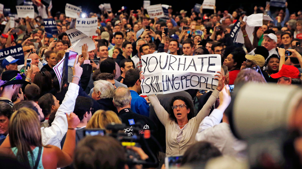 A protestor holds up a sign as Republican presidential candidate Donald Trump speaks at a campaign rally in New Orleans, Friday, March 4, 2016.