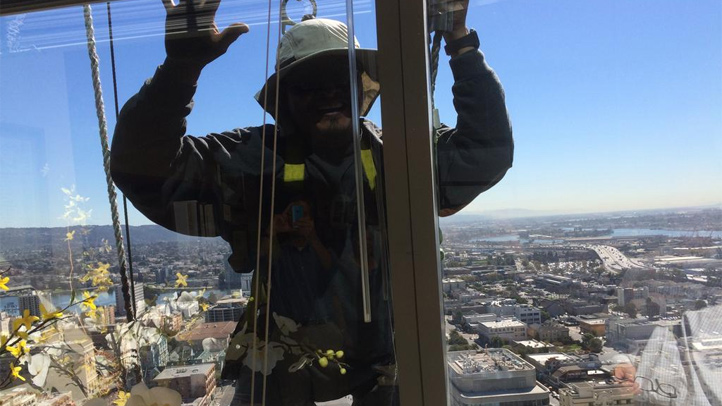 A firefighter rescue two window washer stuck outside 1111 Broadway in downtown Oakland, Thursday, Oct. 2, 2014.