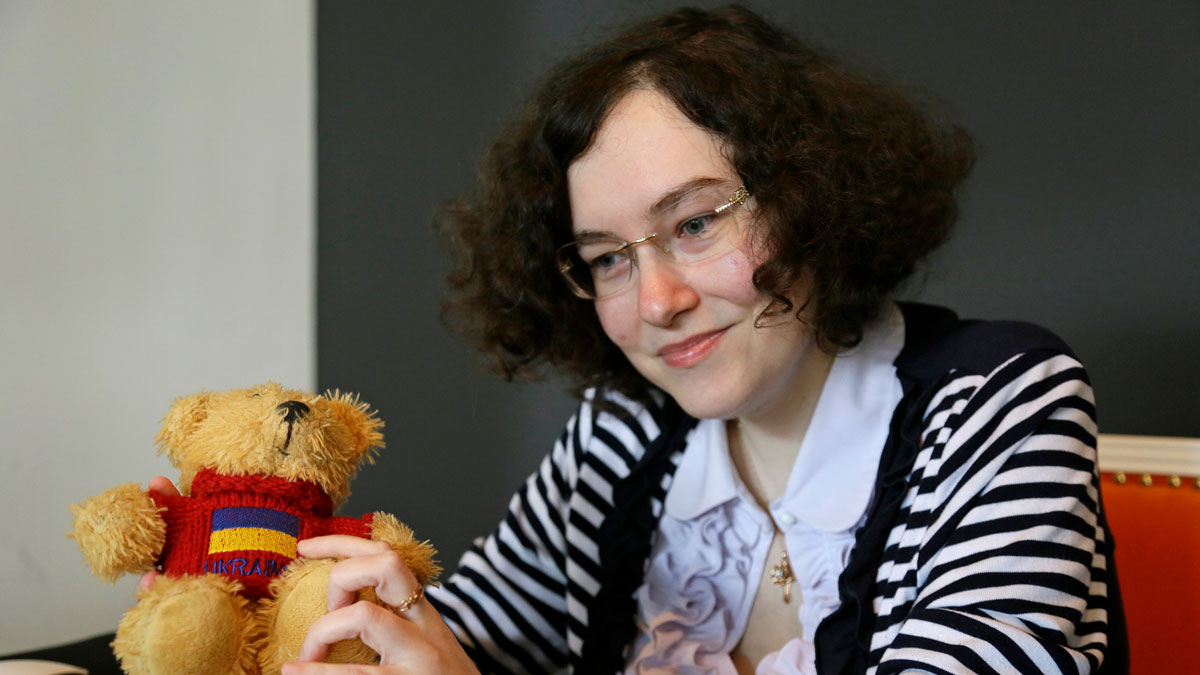 In this photo taken Wednesday, March 22, 2017, Russian journalist-in-exile Kseniya Kirillova looks over a doll that belonged to her late friend, journalist Alexander Schchetinin, in a lobby near her home in Oakland, Calif.