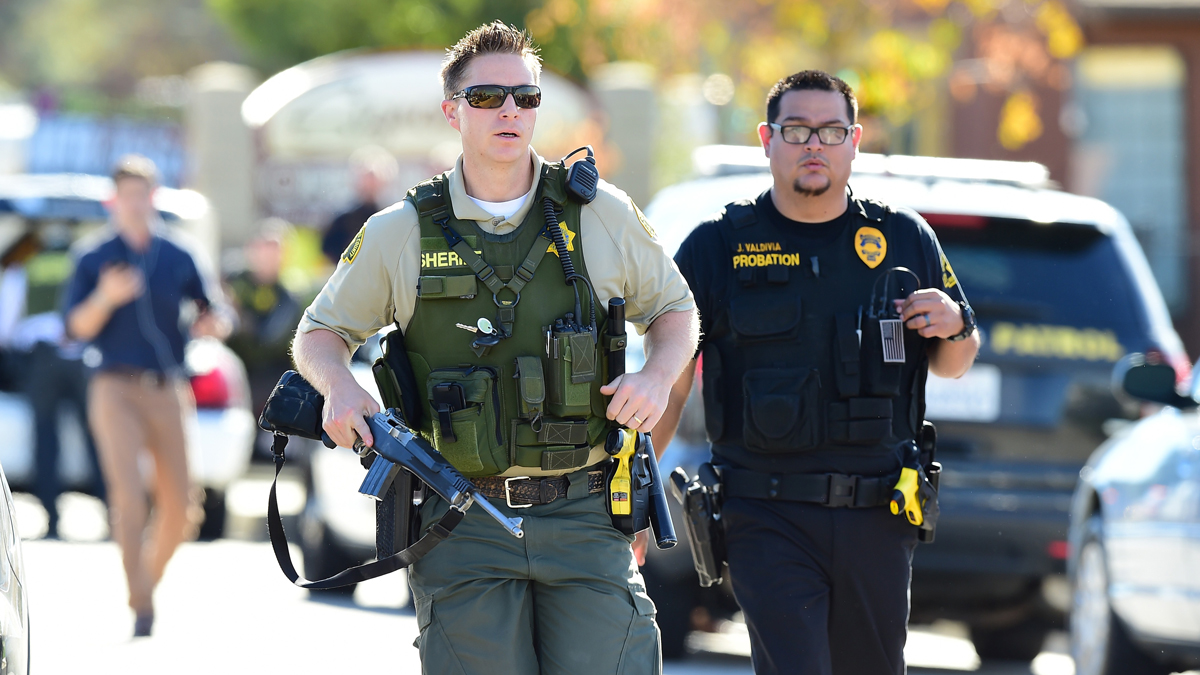 Police at the scene of a shooting on December 2, 2015 in San Bernardino, California. One or more gunman opened fire inside a center that provides services for the disabled in San Bernardino in California, with reports of 14 people killed and 14 additional people wounded. Police were still hunting for the shooter, saying one to three possible suspects were involved. Heavily armed SWAT teams, firefighters and ambulances swarmed the scene, located about an hour east of Los Angeles, as police warned residents away.