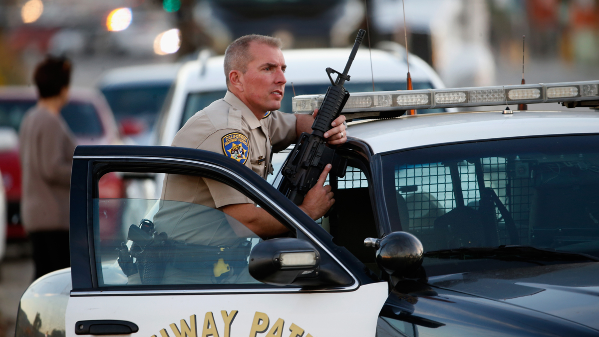 A California Highway Patrol officer stands with his weapon as authorities pursued the suspects in a shooting that occurred at the Inland Regional Center on Dec. 2, 2015 in San Bernardino, California.