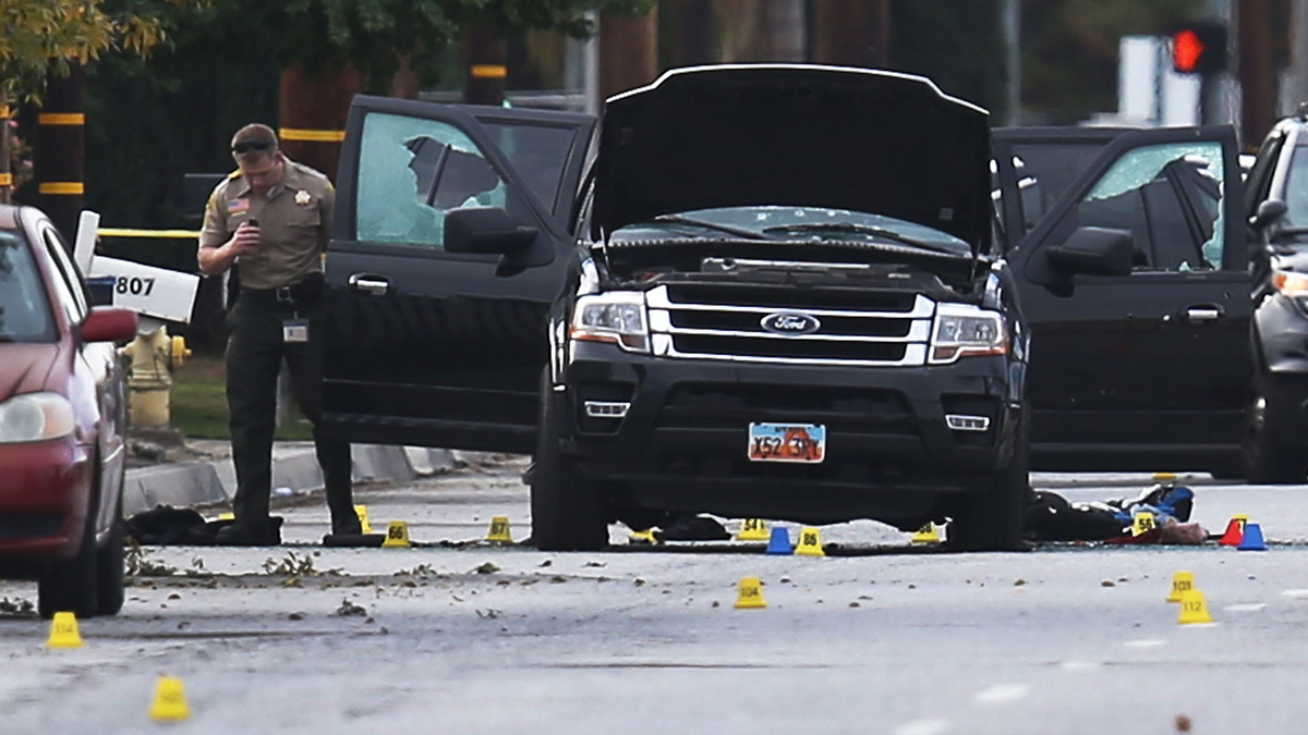In this Dec. 3, 2015, photo, law enforcement officials investigate around the Ford SUV vehicle that was the scene where suspects of the shooting at the Inland Regional Center were killed in San Bernardino, California.