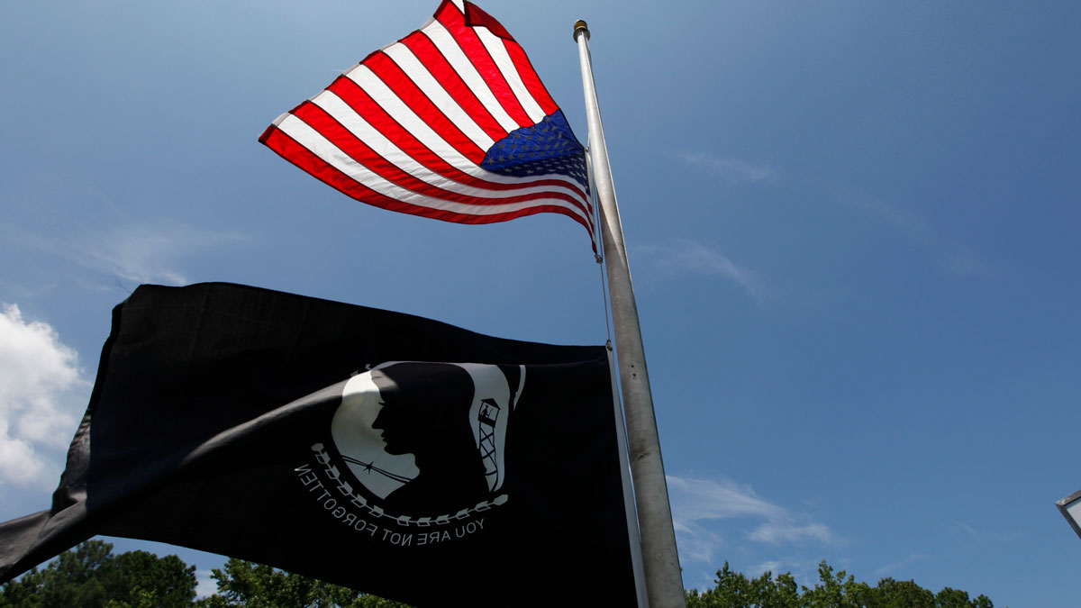 A US flag and a POW/MIA flag is flown at half staff outside a sports bar near the main gate of Naval Air Station Oceana Dam Neck Annex the base of Navy Seal Team six in Virginia Beach , Va., Monday, Aug. 8, 2011.