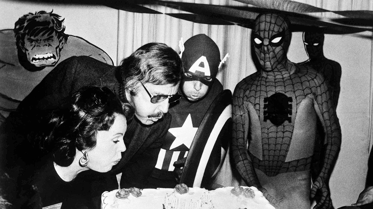 Mighty Marvel comic book publisher, Stan Lee, center left, blows out the candles on the Marvel Comics birthday cake at opening day ceremonies of the First Mighty Marvel Comic Book Convention, March 22, 1975, New York. At left is Lee's wife Joan and on the far right, Spider-Man. Another Marvel Superhero, Captain America looks on from the rear. (AP Photo)