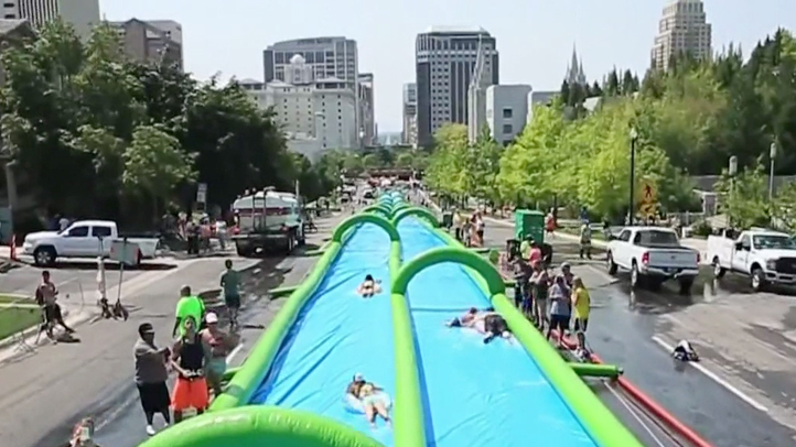A still of a water slide in a promotional video by Slide the City.