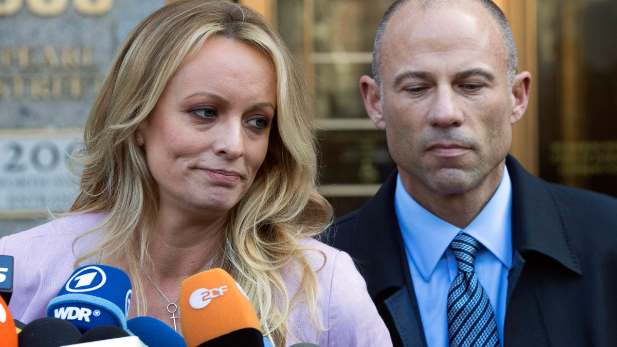 In this April 16, 2018 file photo, adult film actress Stormy Daniels, whose given name is Stephanie Clifford, and her attorney Michael Avenatti talk to reporters outside federal court in New York City.