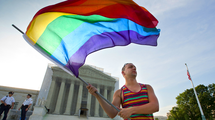 Gay rights advocate Vin Testa waves a rainbow flag in front of the Supreme Court at sun up in Washington, Wednesday, June 26, 2013.