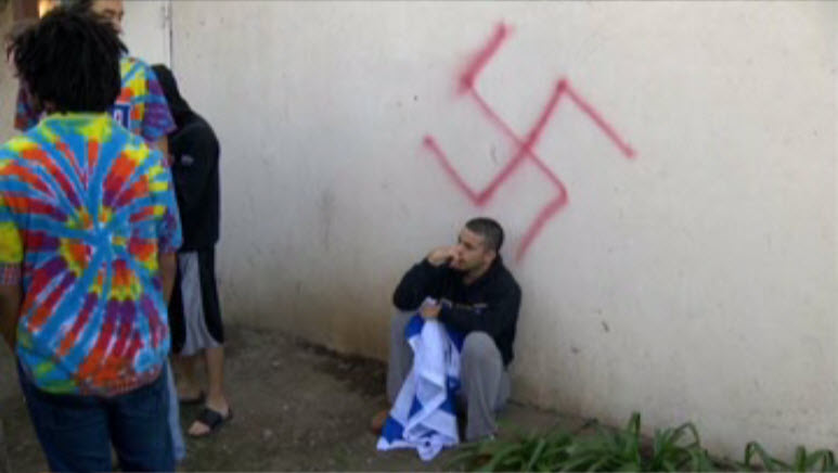 A student with an Israeli flag sits underneath a swastika painted on Alpha Epsilon Pi fraternity discovered on Jan. 31.