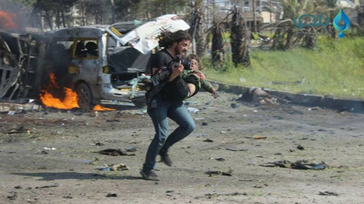 Abd Alkader Habak is photographed carrying a wounded Syrian boy.