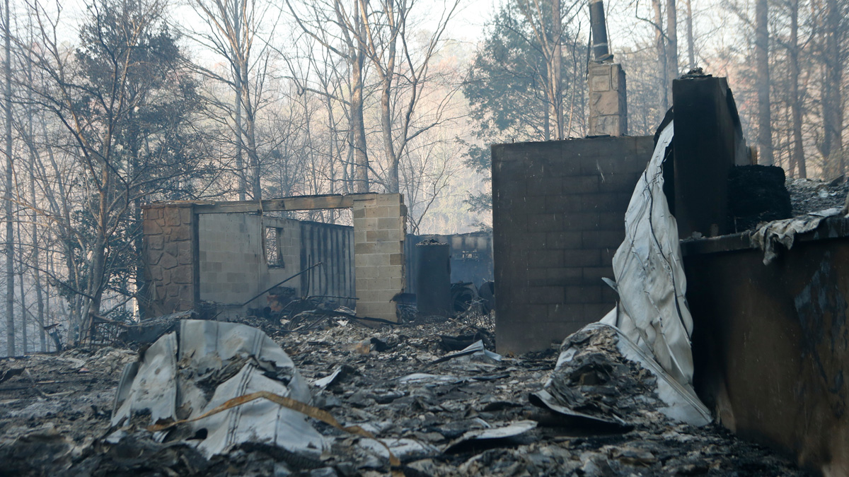 The remains of a home smolders after a wildfire Nov. 29, 2016, in Gatlinburg, Tennessee. Thousands of people have been evacuated from the area and over 100 houses and businesses were damaged or destroyed after drought conditions helped the fire spread through the foothills of the Great Smoky Mountains.