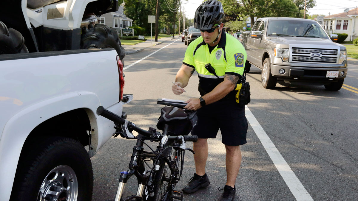 In this Wednesday, July 20, 2016 photo, police officer Matthew Monteiro writes a citation for a motorist who was texting while driving, after pulling the vehicle over while patrolling on his bicycle in West Bridgewater, Mass.