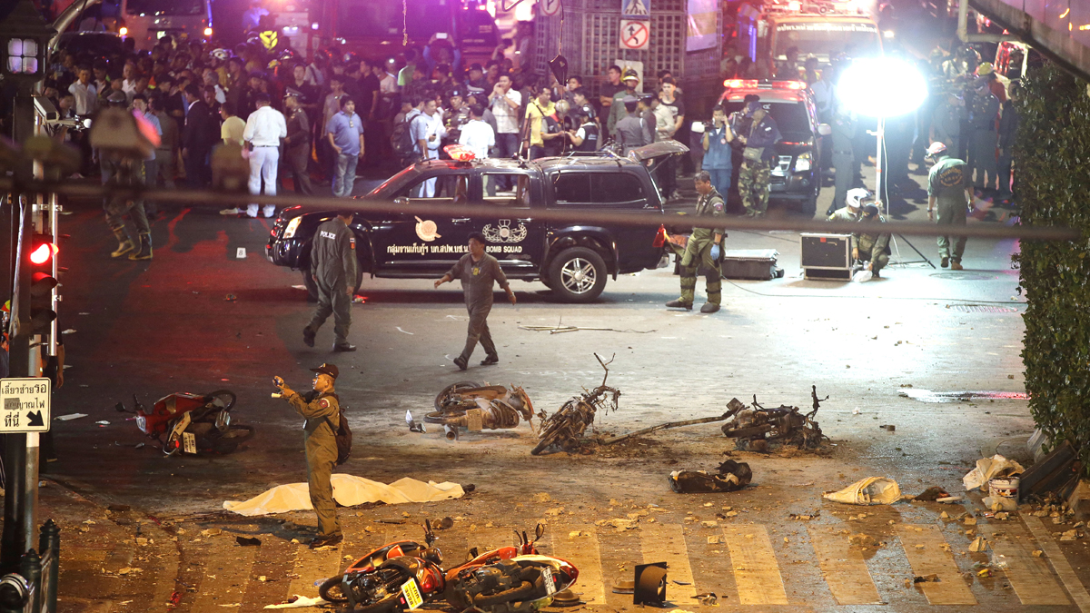 A policeman photographs debris from an explosion in central Bangkok, Thailand, Monday, Aug. 17, 2015. A large explosion rocked a central Bangkok intersection during the evening rush hour, killing a number of people and injuring others, police said.