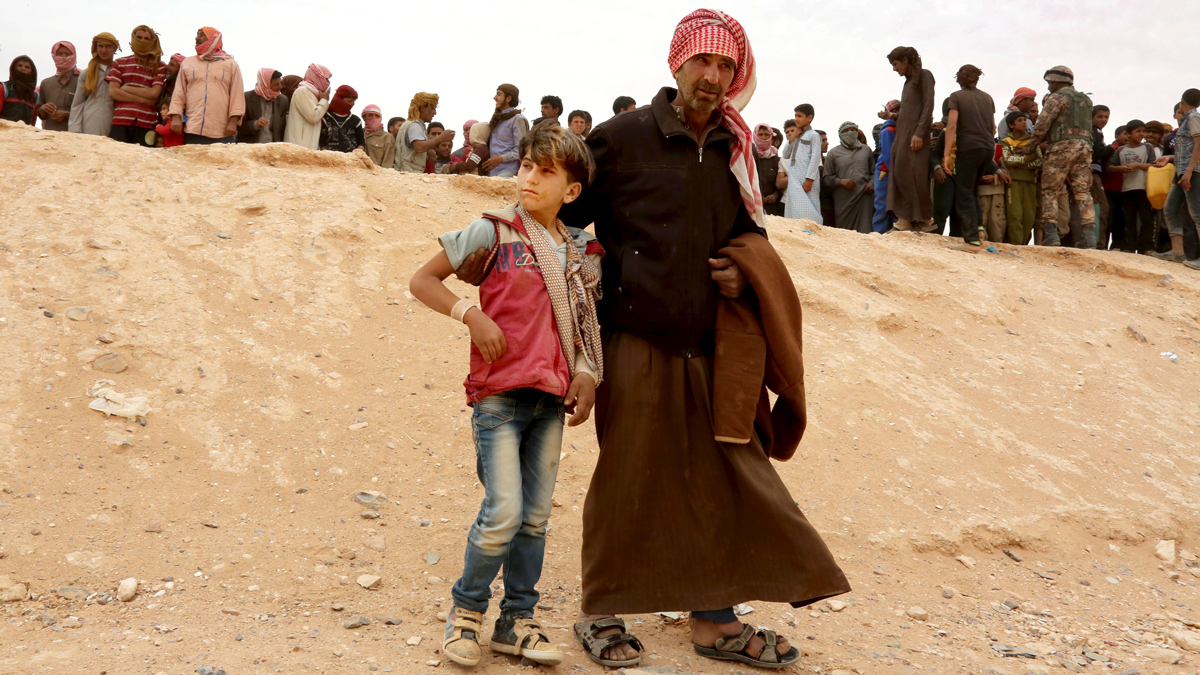 A Syrian refugee man and boy cross into Jordan at the Hadalat reception area on the Syrian-Jordanian border, about 320 kilometers (200 miles) northeast of the capital of Amman, Wednesday, May 4, 2016. The commander of Jordan's Border Guard Forces says the number of Syrian refugees amassed in remote desert areas on the Jordanian border and waiting to enter has risen to a new high of 59,000.