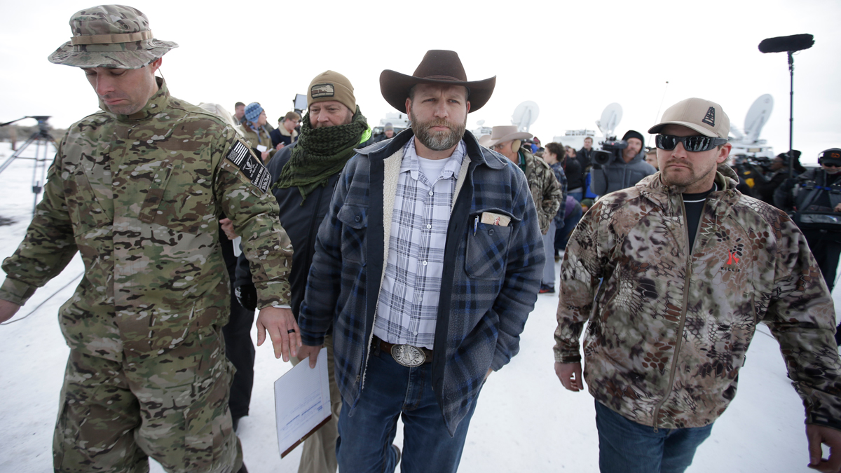 Ammon Bundy, center, one of the sons of Nevada rancher Cliven Bundy, walks off after speaking with reporters during a news conference at Malheur National Wildlife Refuge headquarters Monday, Jan. 4, 2016, near Burns, Oregon.