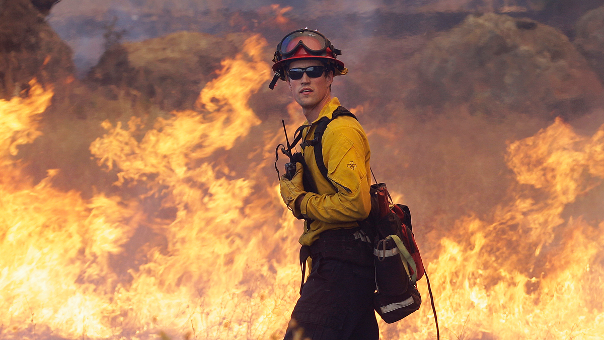Garden Valley firefighter Chris Schwegler walks by flames along Morgan Valley Road near Lower Lake, Calif., Thursday, Aug. 13, 2015. Crews battling the wind-stoked blaze took advantage of cooler temperatures Thursday to clear brush and expand containment lines with bulldozers and hand tools.