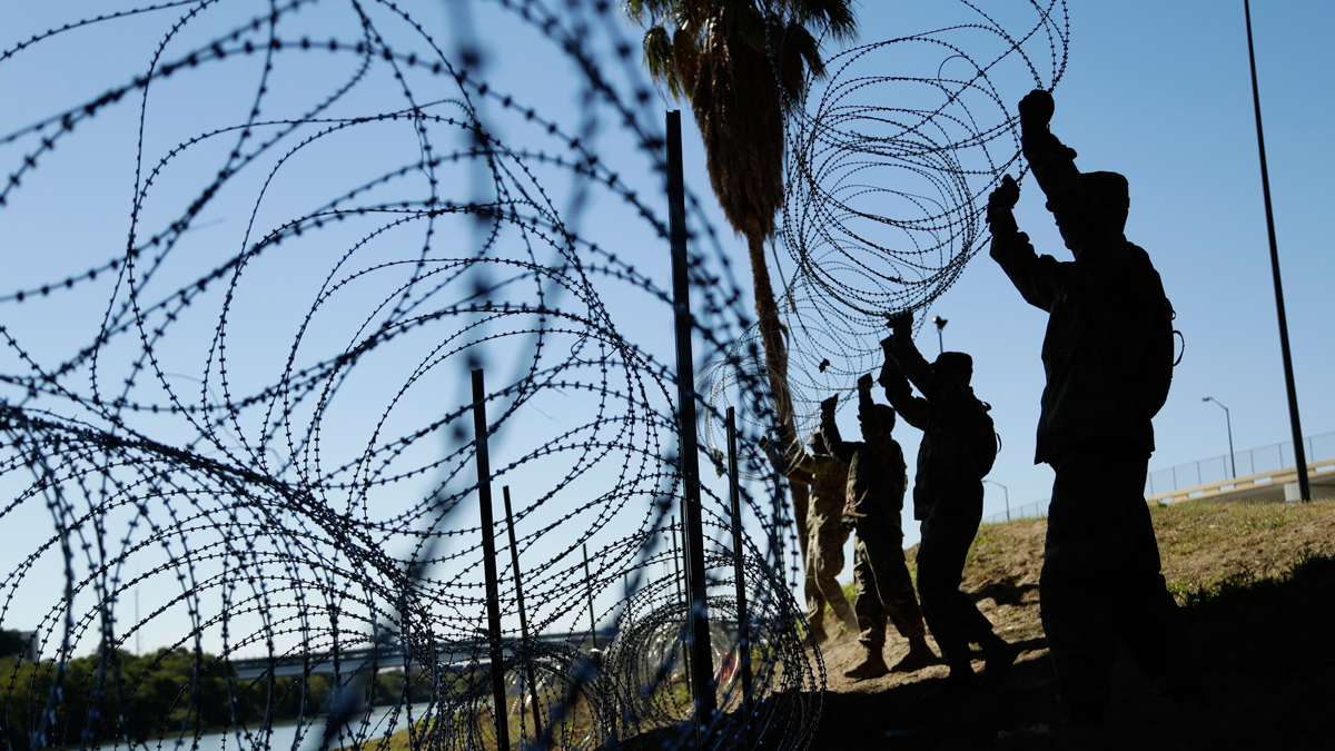 In this Friday, Nov. 16, 2018, file photo, members of the U.S. military install multiple tiers of concertina wire along the banks of the Rio Grande near the Juarez-Lincoln Bridge at the U.S.-Mexico border in Laredo, Texas.