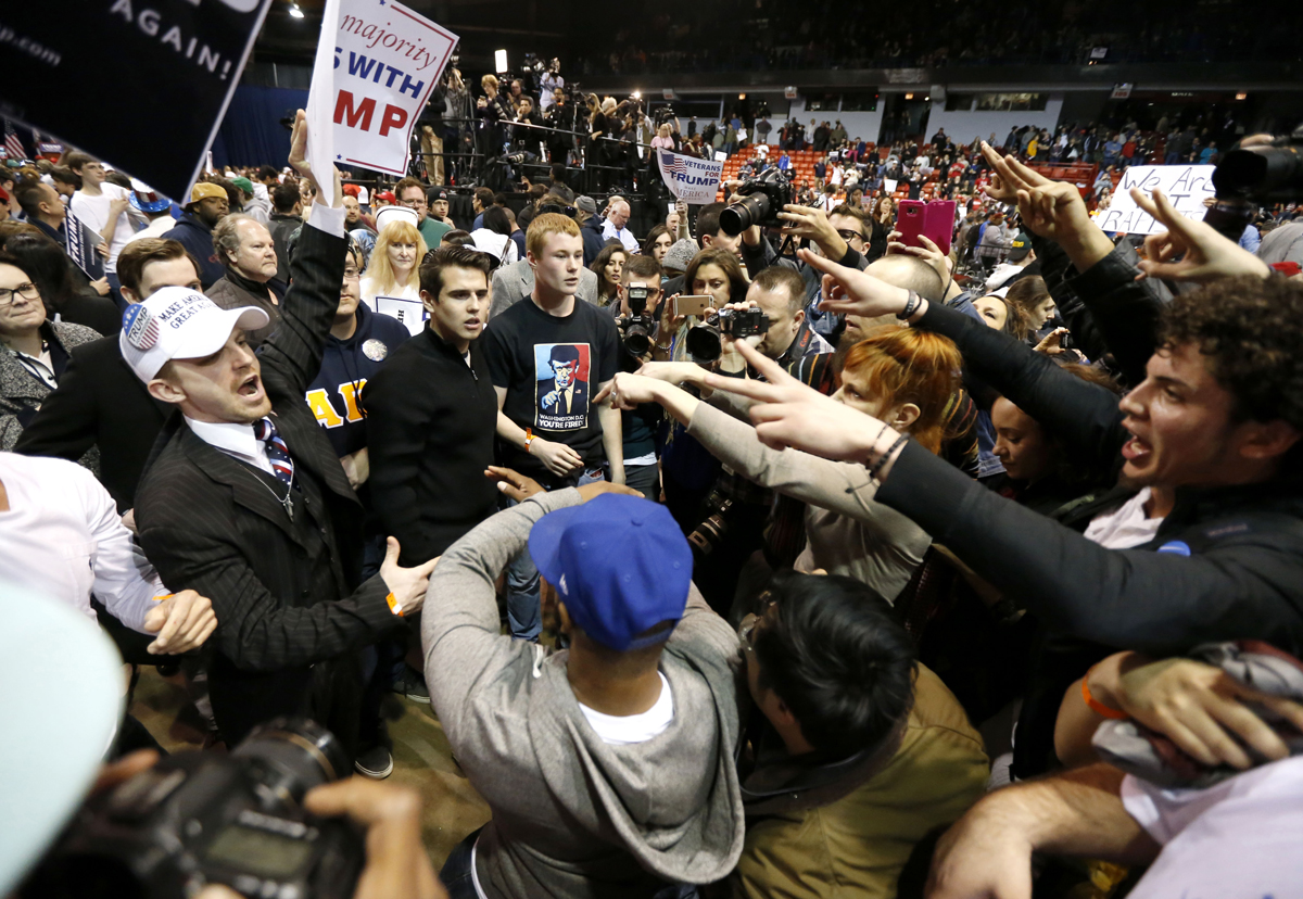 Supporters of Republican presidential candidate Donald Trump, left, face off with protesters after a rally on the campus of the University of Illinois-Chicago was cancelled due to security concerns Friday, March 11, 2016, in Chicago.