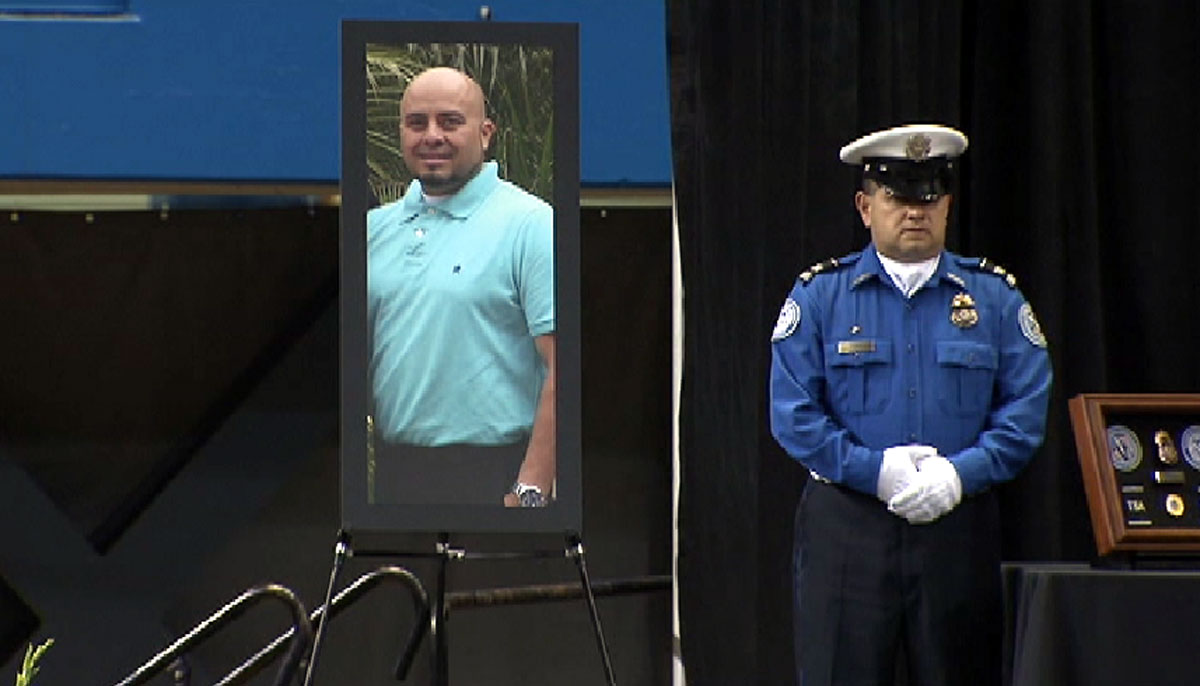 A TSA employee stands next to an image of Gerardo Hernandez at the slain TSA officer's memorial service on Tuesday Nov. 12, 2013 in Los Angeles. Hernandez's family is suing Los Angeles authorities for his wrongful death, according to a lawsuit filed Tuesday Oct. 7, 2014.