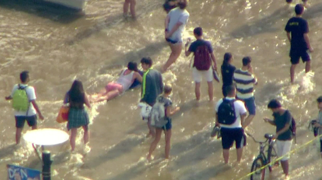 A water main rupture sent water rushing onto Sunset Boulevard, stranding drivers and flooding the UCLA campus on Tuesday, July 29, 2014.