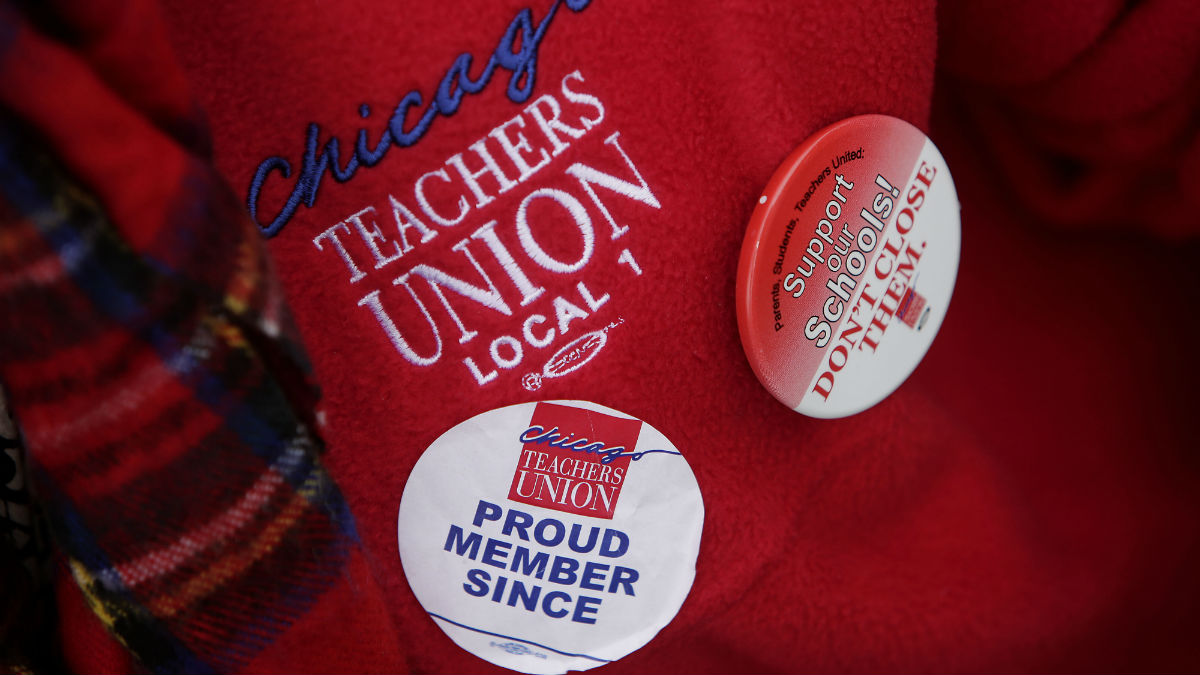 A Chicago teacher picketing during a one-day strike wears a Chicago Teachers Union Local 1 sweater and a sticker and button on April 1, 2016 in Chicago, Illinois. Chicago teachers and the Chicago Teachers Union Local 1 are demanding that lawmakers provide the funding needed for proper education and other programs. The strike affect over 300,000 students across the city.